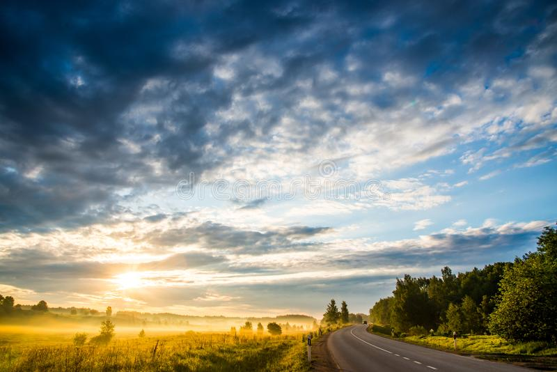 Sunrise landscape of sky, road and field royalty free stock image