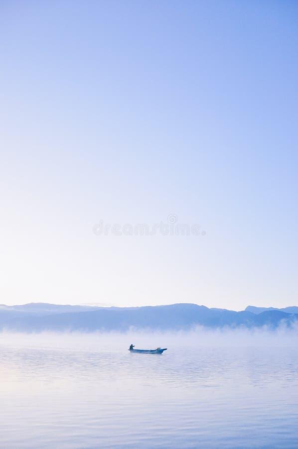 Sunrise at lugu lake. Foggy morning. Boat stock image