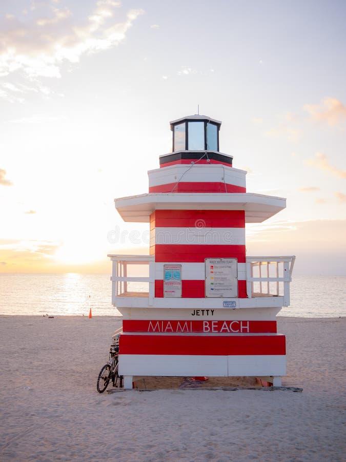 Sunrise in Miami Beach Florida, mit einem bunten Rettungsschwimmerhaus in einer typischen Art-Déco-Architektur, bei Sonnenaufgang lizenzfreies stockbild