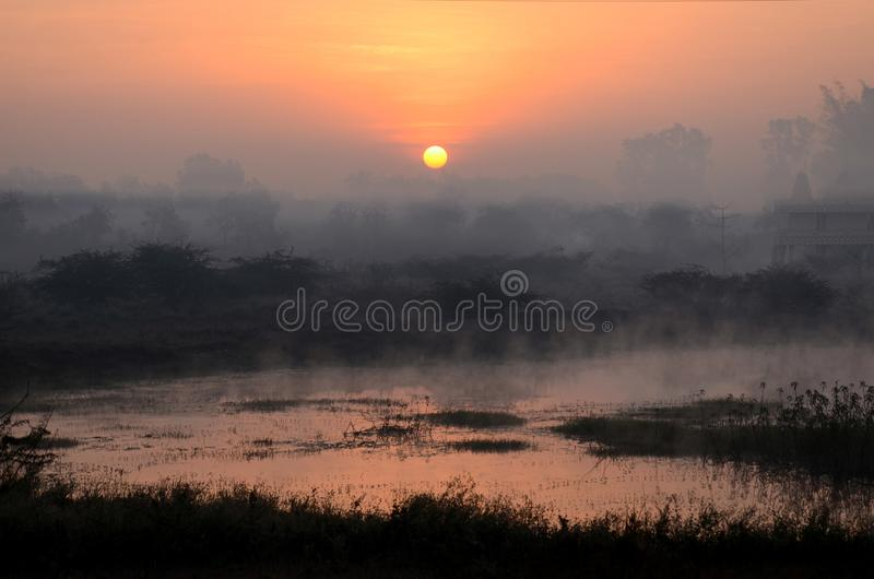 Sunrise dramatic blue sky with orange sun rays breaking through the clouds. Sunrise  is the moment when the upper limb of the Sun appears on the horizon in the royalty free stock photography