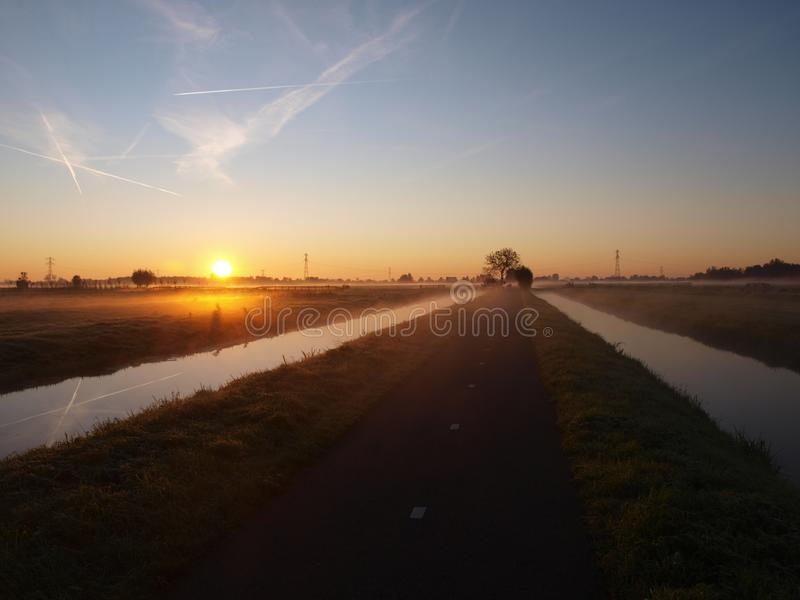 Sunrise with morning fog over the meadows of the polder at Goudarak close to Gouda in the Netherlands. stock photos