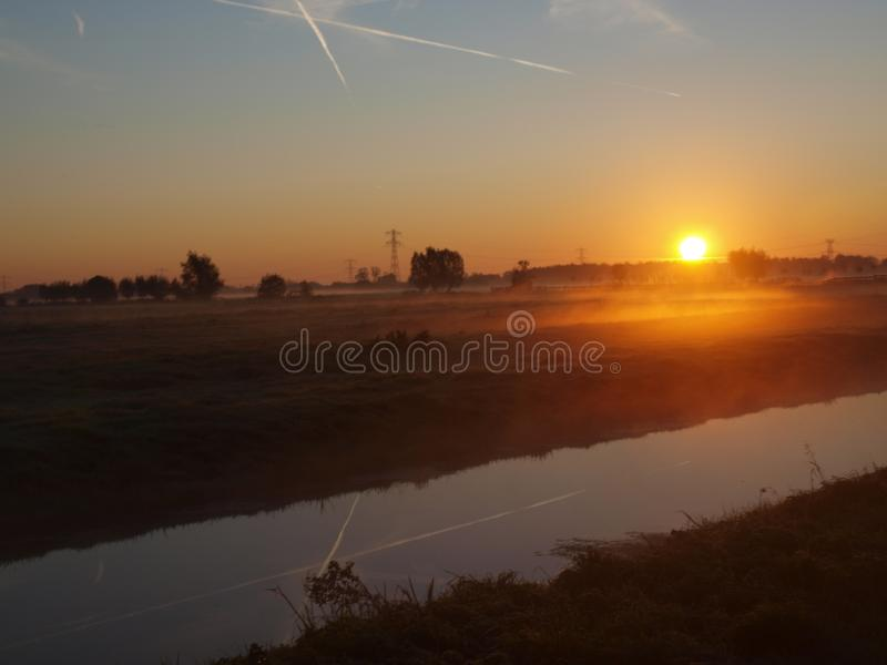 Sunrise with morning fog over the meadows of the polder at Goudarak close to Gouda in the Netherlands. royalty free stock image