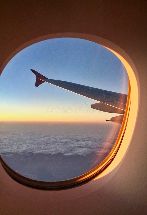 Sunrise Shining on Airplane Wing and Window royalty free stock photo