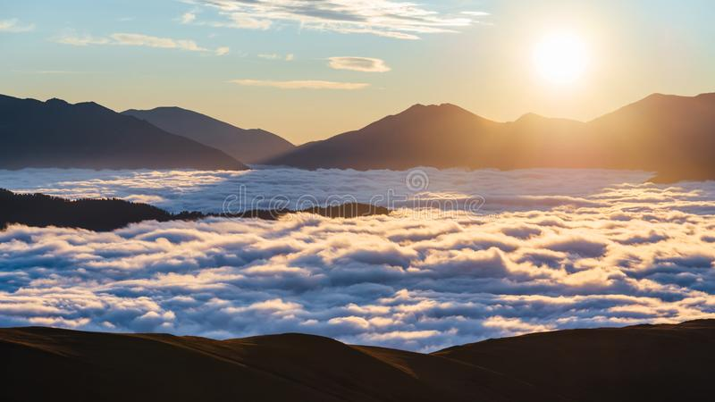 Sunrise in the mountains. Clouds between the mountains below, the sun in the frame. The clouds below between the mountain ranges are illuminated by the rays of royalty free stock photography