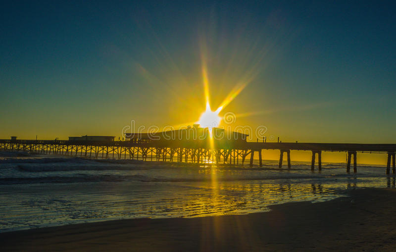 Sunrise near the dock. Photo taken last year near the dock near Daytona beach, Florida. It was early, the sun was rising and it was quiet on the beach royalty free stock images