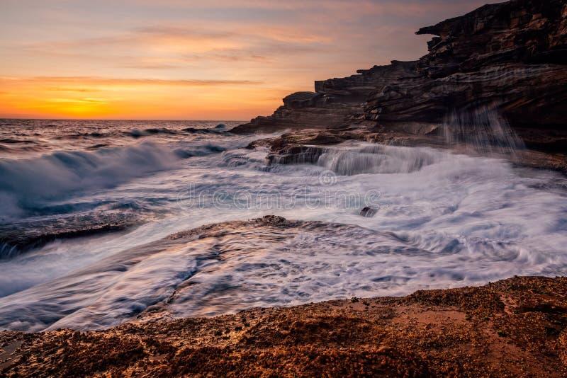 Sunrise and ocean cascades along coastal rocks and headland royalty free stock photo