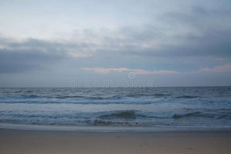 Sunrise on the ocean, white sky, and sand royalty free stock photos