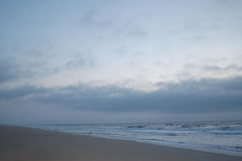 Sunrise on the ocean, white sky, and sand stock photo