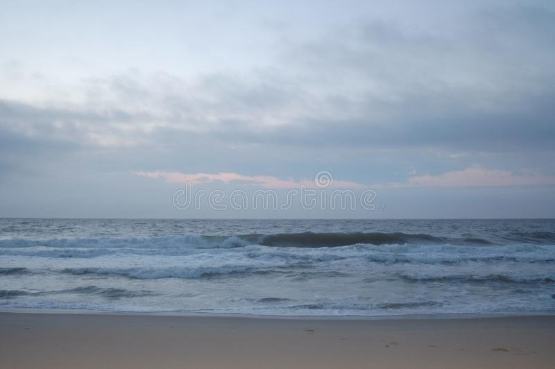 Sunrise on the ocean, white sky, and sand stock image