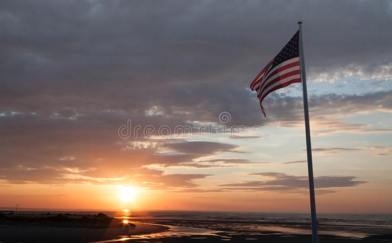 Sunrise at Ogunquit Maine with American Flag. A beautiful sunrise in Ogunquit Maine with American flag flying and ocean view of tides and beach stock images