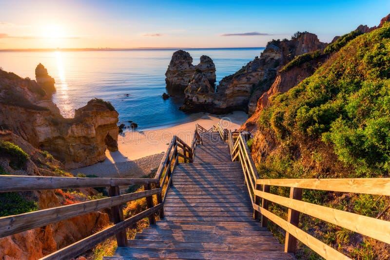 Sunrise op het strand van Camilo in Lagos, Algarve, Portugal Woodenbrug naar het strand Praia do Camilo, Portugal Afbeeldingsweer royalty-vrije stock afbeelding