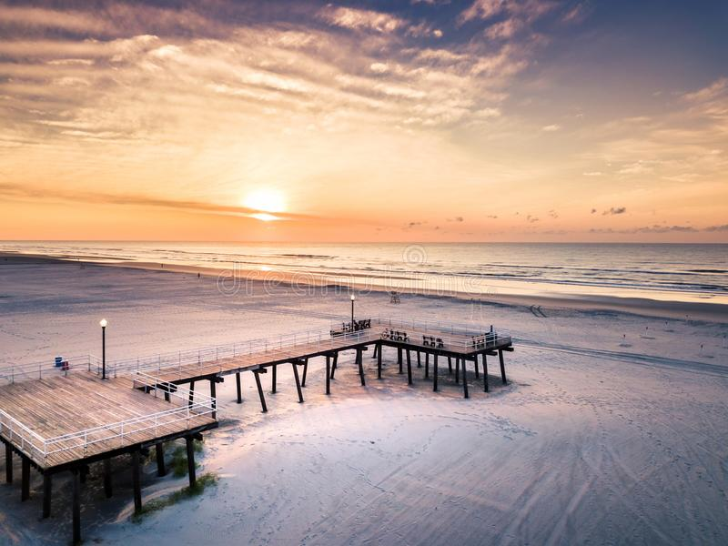Sunrise over the beach and wooden dock aerial view royalty free stock images