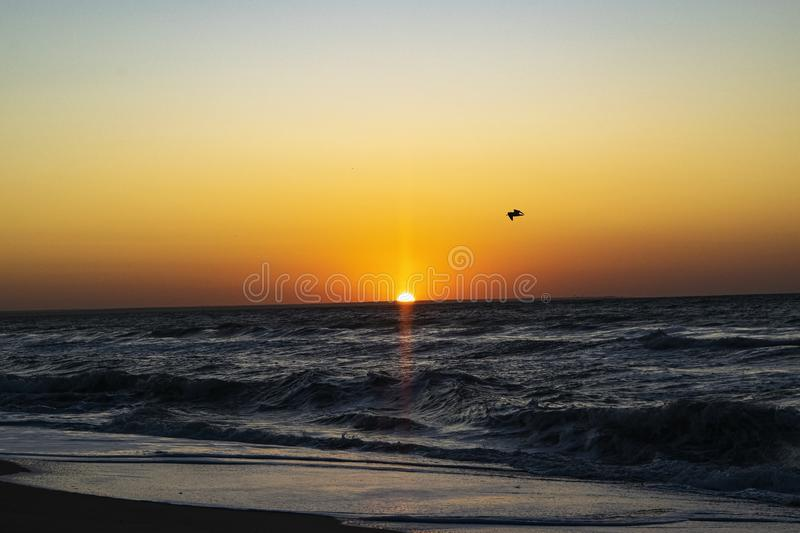 Sunrise over the Black sea, waves on the sandy beach.  royalty free stock photography