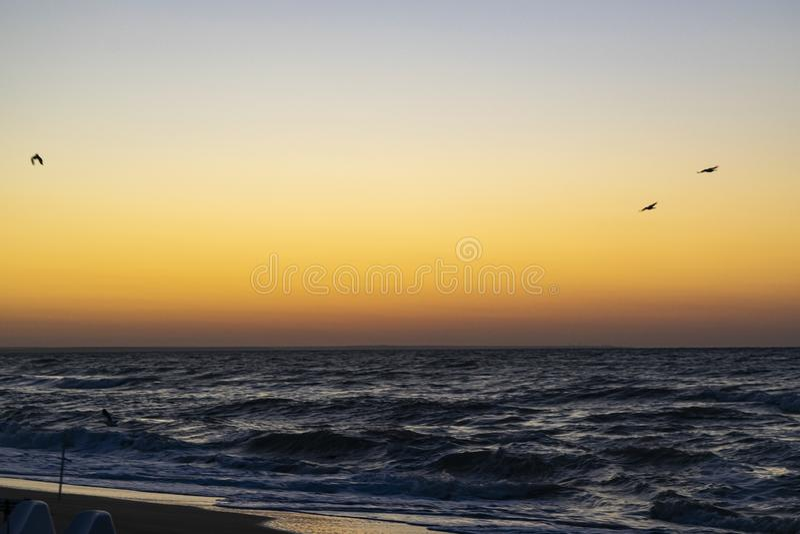 Sunrise over the Black sea, waves on the sandy beach.  royalty free stock photo