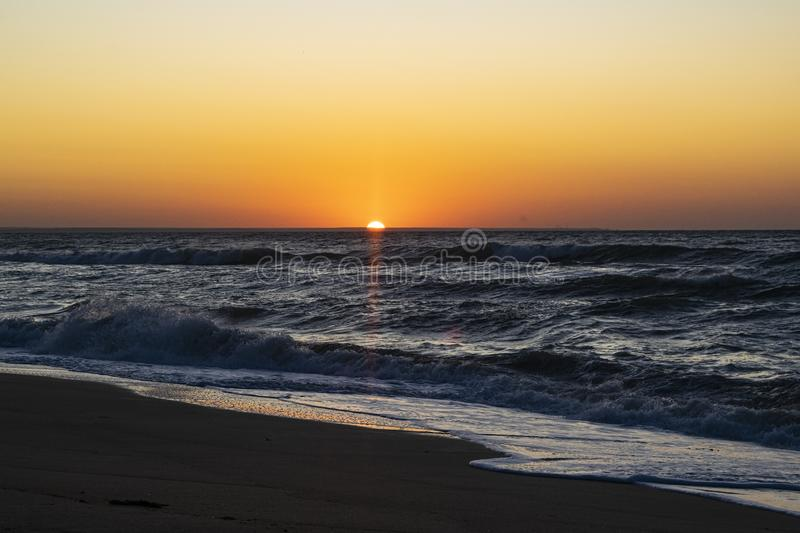 Sunrise over the Black sea, waves on the sandy beach.  royalty free stock image