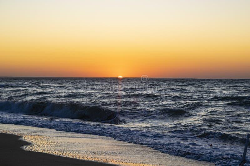 Sunrise over the Black sea, waves on the sandy beach.  stock photos