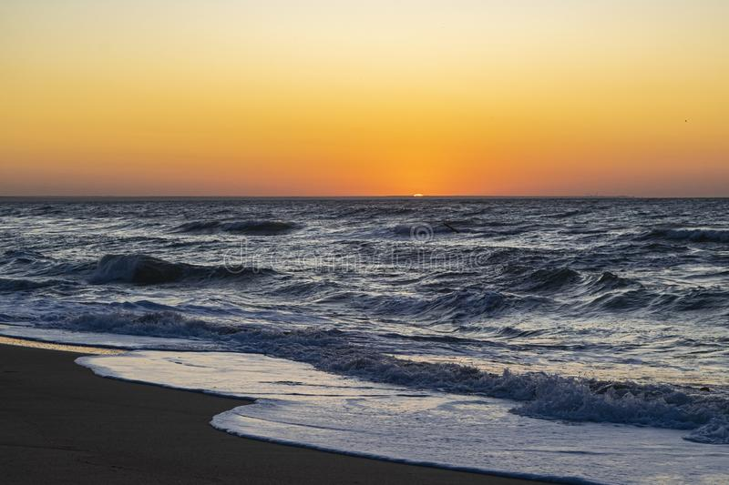 Sunrise over the Black sea, waves on the sandy beach.  royalty free stock images