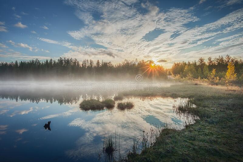 Sunrise over a blue lake and fog in the background. stock photo