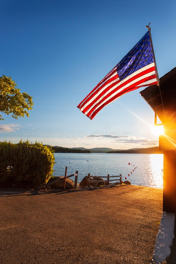 Sunrise over boat ramp and flag royalty free stock photography