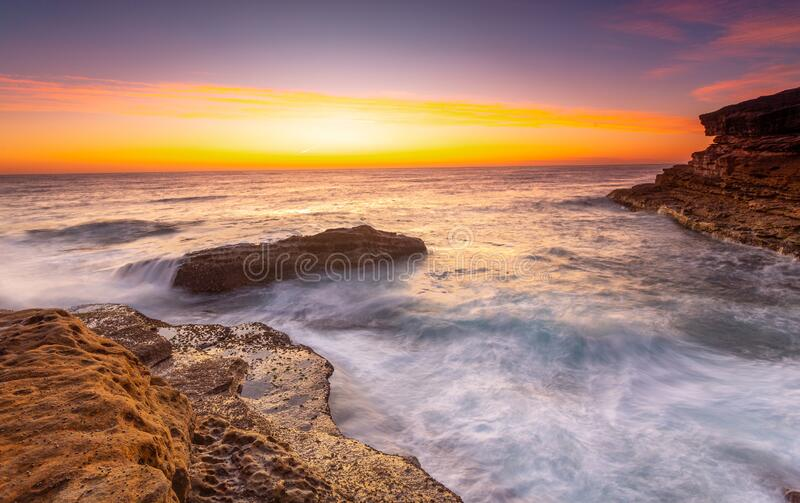 Sunrise over the ccean with some foreground rocks of eroded sandstone stock photography