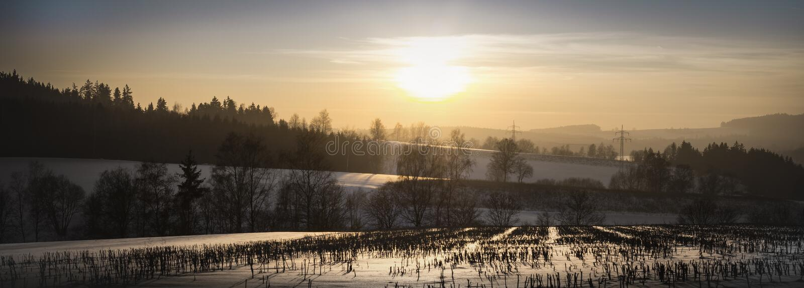 Sunrise over a cold snowy winter landscape. Panoramic view of a glowing orange sunrise over a cold snowy winter landscape with leafless deciduous trees on royalty free stock photo