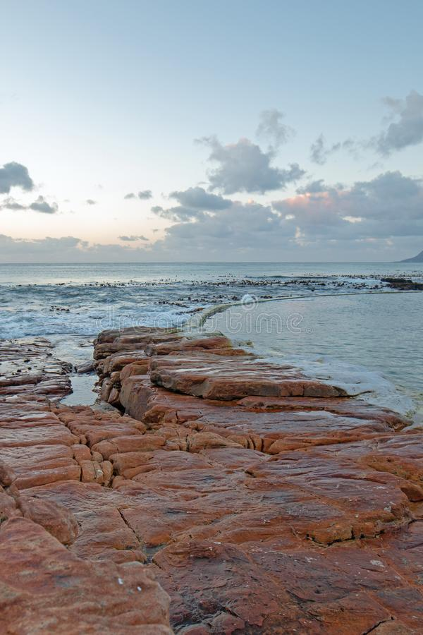 Sunrise over rocky coast at Dale Brook Tidal Swim Pool seawall in Cape Town South Africa SA royalty free stock images
