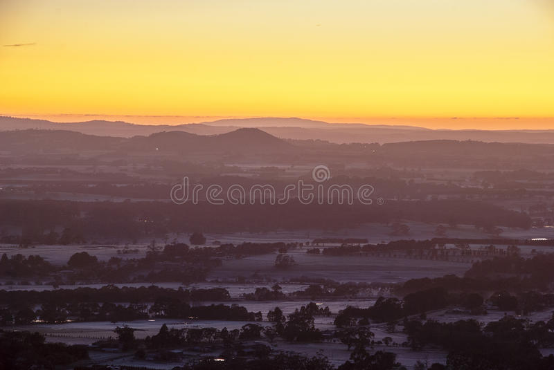 Sunrise over distant hills. Sun about to peek over the horizon with a brilliant orange sky and frosty meadows royalty free stock image