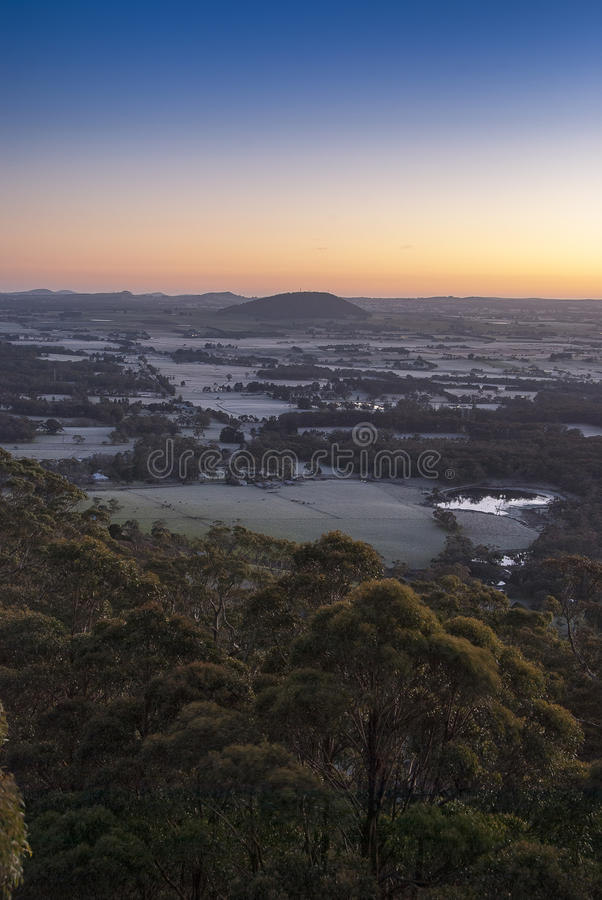 Sunrise over distant hills. Sun about to peek over the horizon with a brilliant orange sky and frosty meadows royalty free stock photography