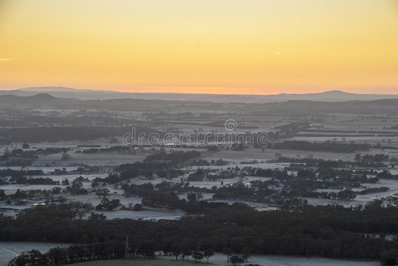 Sunrise over distant hills. Sun about to peek over the horizon with a brilliant orange sky and frosty meadows royalty free stock photo