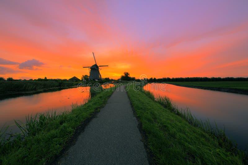 Sunrise over a Dutch landscape. Burning orange and res sky above a dutch windmill