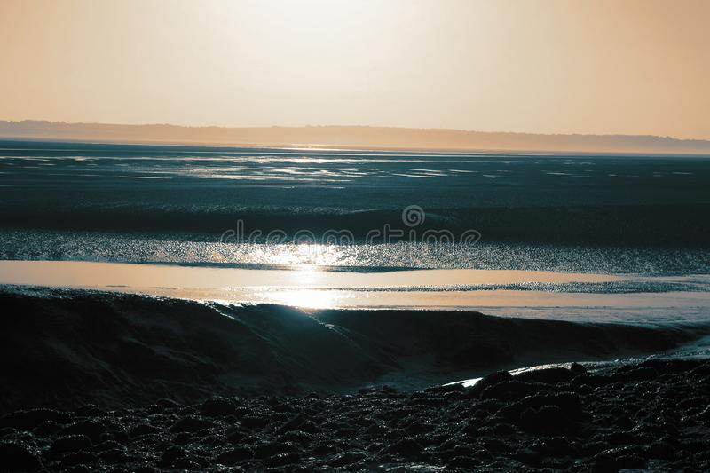 Sunrise over an estuary beach with the sunlight reflected on the water. royalty free stock photography