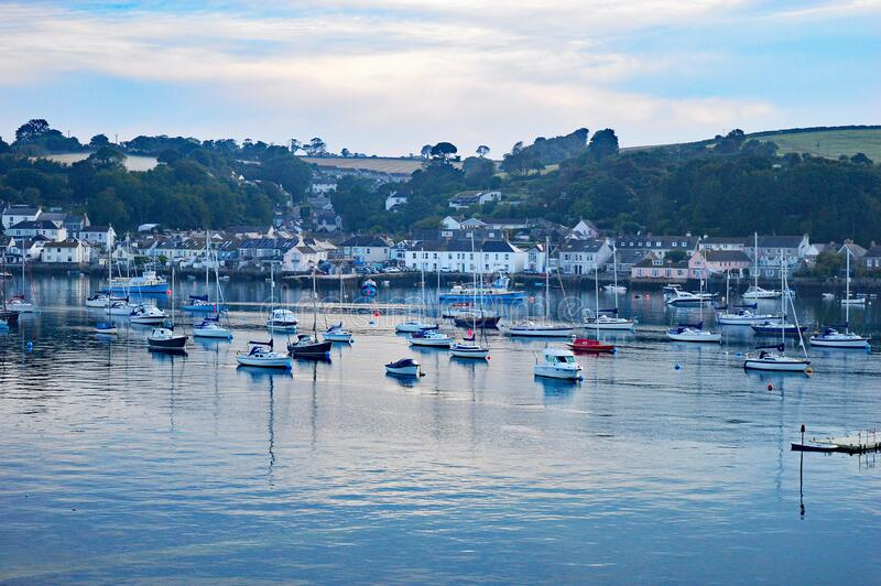 Sunrise over Flushing, Cornwall UK. Dawn rises over the small fishing village of Flushing near Falmouth on the river Penryn. Small boats moored in the water royalty free stock photos