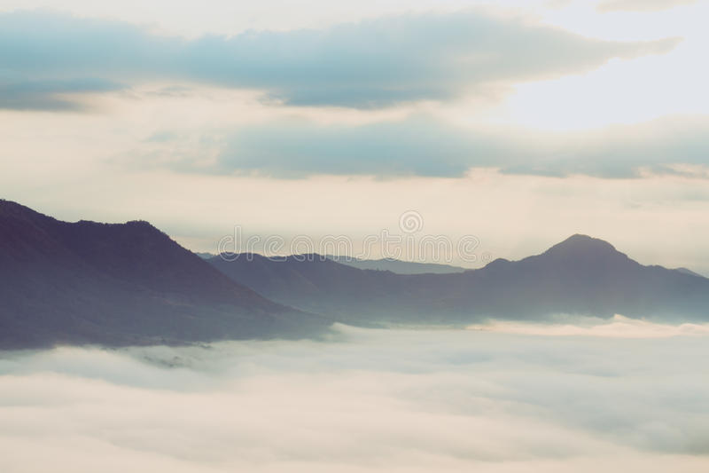 Sunrise over foggy mountain valley, Thailand. Sunrise over foggy mountain valley with blue skies in Thailand stock photo