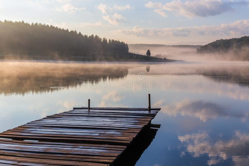 Sunrise over the foggy river with a wooden pier royalty free stock photos