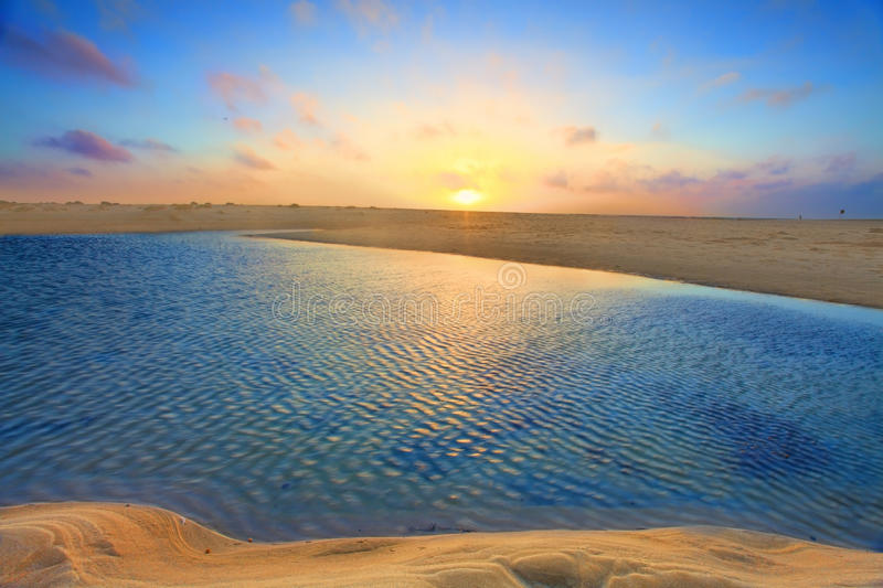 Sunrise over golden sands and azure waters royalty free stock images