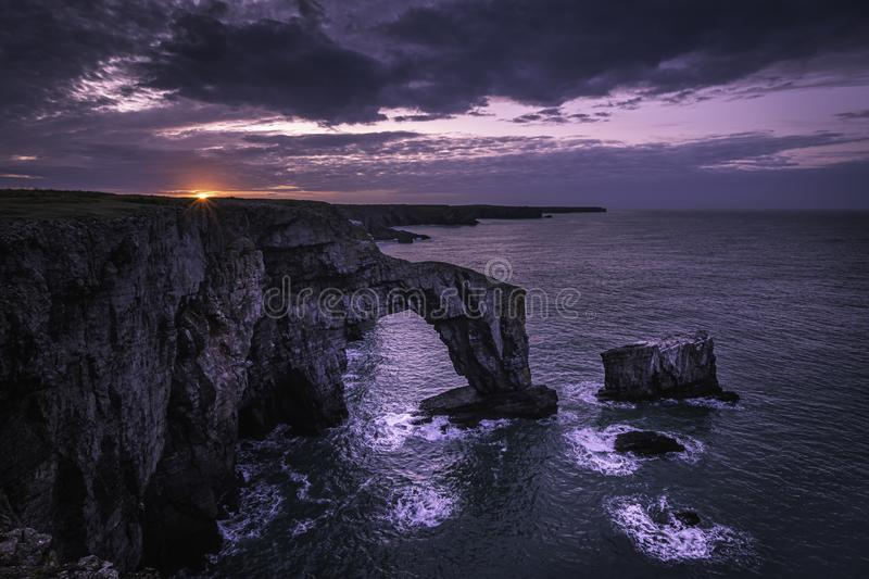 Sunrise over Green Bridge of Wales, Pembrokeshire,South Wales, UK. Sunrise over Green Bridge of Wales, famous, natural rock arch, popular landmark and tourists stock photography