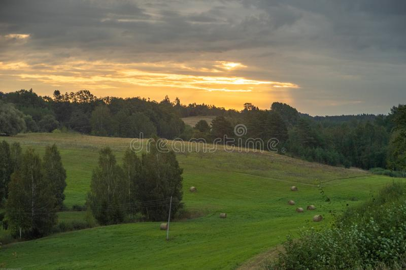 Sunrise over green hills with hay fields an forests in summer morning. Sunrise light breaking through the grey clouds over hay fields with bales of hay royalty free stock photography