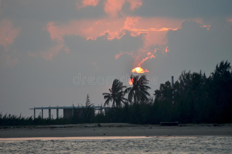 The sun rising through clouds, over a tropical beach with a shack. royalty free stock images
