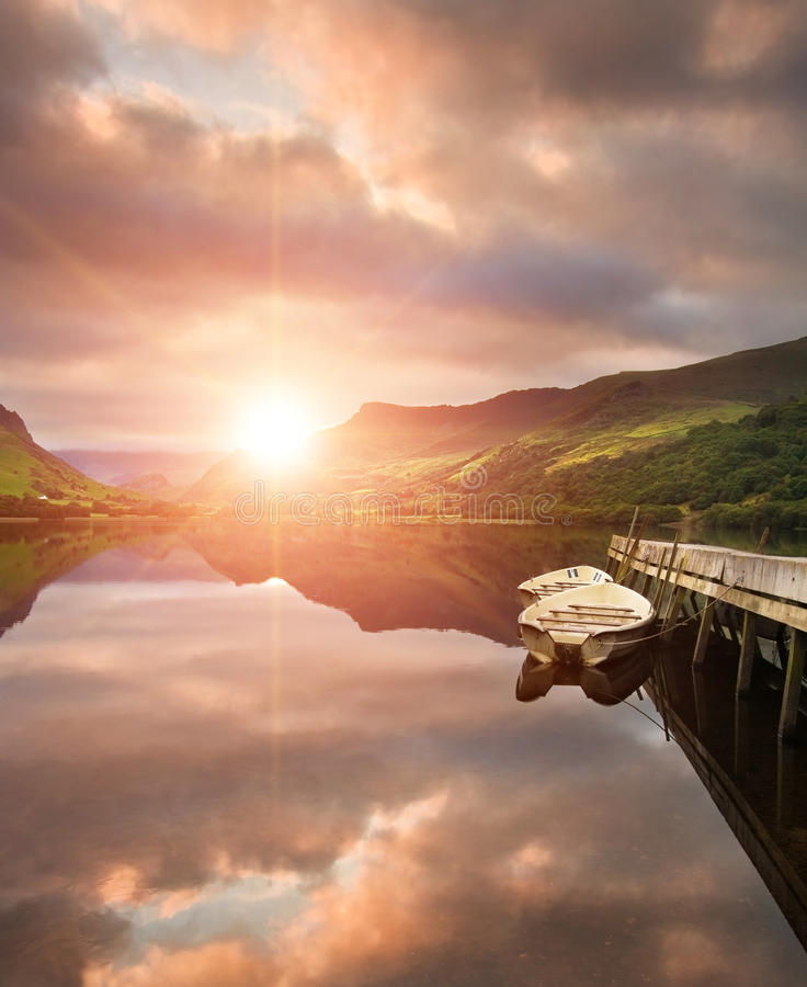 Sunrise over lake with boats moored at jetty stock images