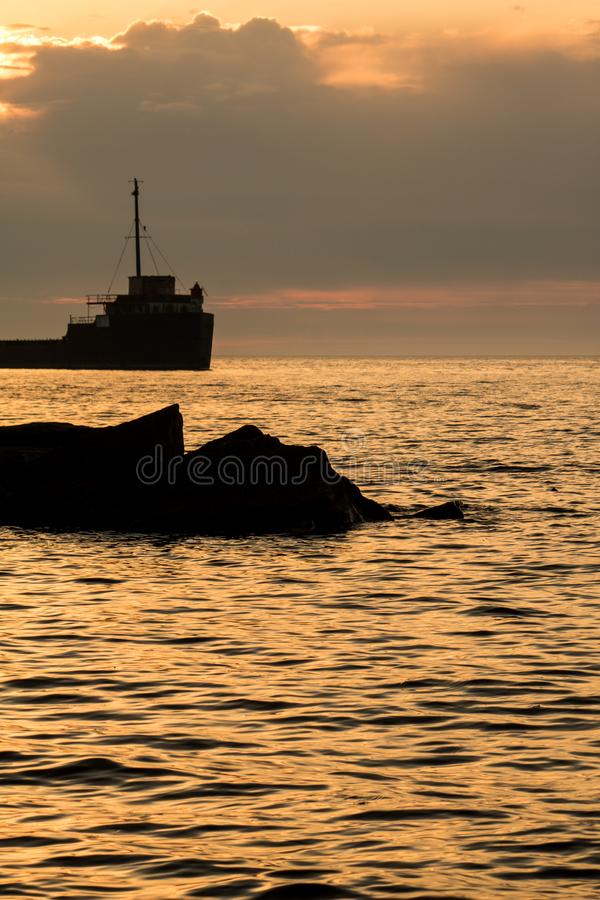 Shoreline Rocks And A Great Lakes Freighter At Sunrise. The sunrise over Lake Ontario at Port Credit, Ontario, part of the city of Mississauga. The ship is the stock images