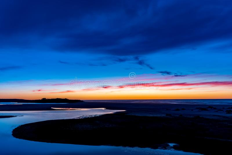 Sunrise over Lake Tyers. A water way creates a striking curve around the edge of the frame as beautiful colours paint the sky before the sun rises over the ocean royalty free stock image