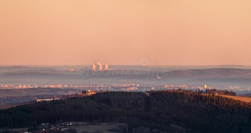 Sunrise over landscape - forest and hill with church in the foreground and nuclear power plant on the horizon. Sunrise over landscape - forest and hill with royalty free stock image