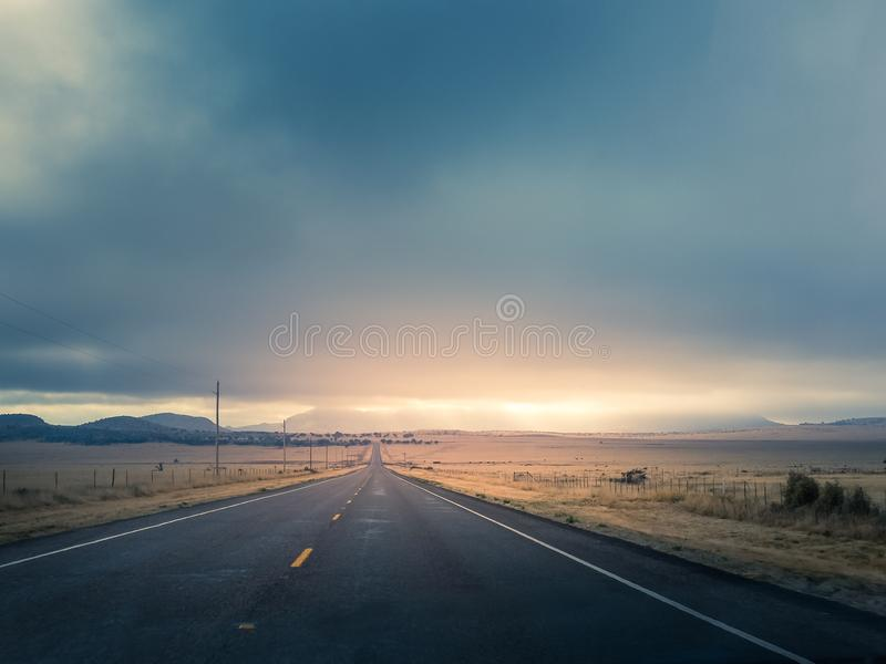 Sunrise and the Open Road. Sunrise over a lonely straight road in West Texas with low clouds royalty free stock photo
