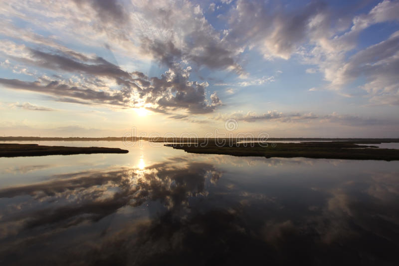 Sunrise over marshes. The sun rising behind clouds is reflected in the water of the marshes near the Bodie Island lighthouse at Cape Hatteras National Seashore stock photos