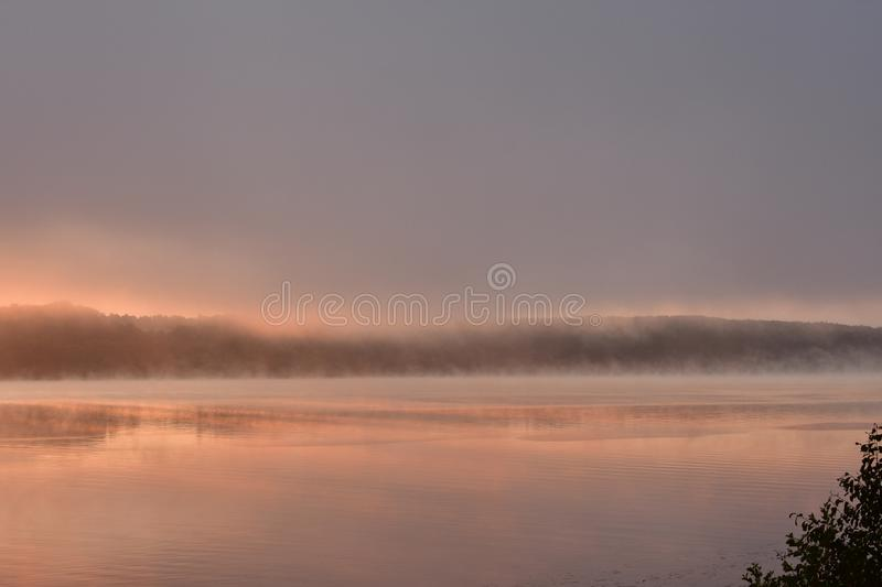Sunrise over the misty river, a solemn moment on the bright stock photos