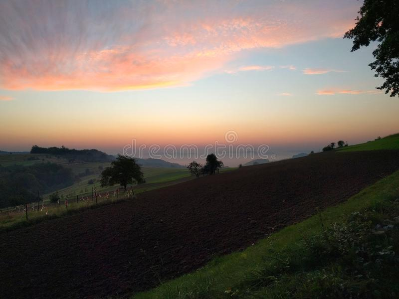 Sunrise over mountain farmland. Sunrise over farmland. Sunrise, summer, spring, morning, fog, sky, cereal, crain, hill, pasture, mist, grass, nature, landscape stock image