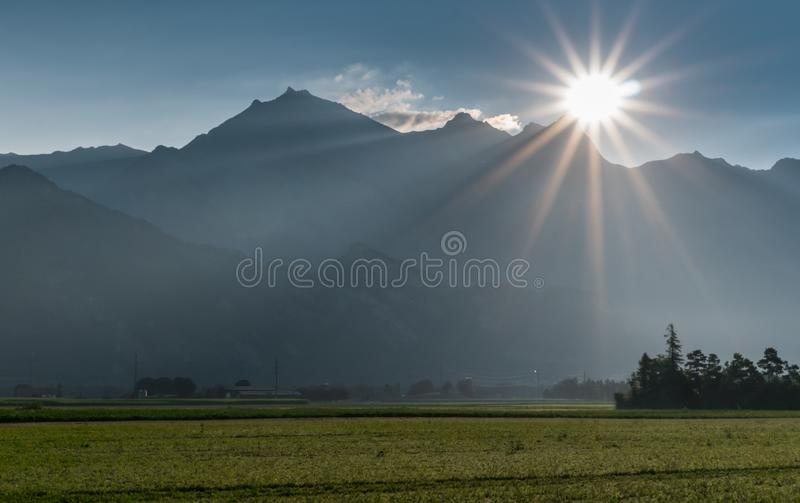 Sunrise over mountains and farm fields in Switzerland stock photos