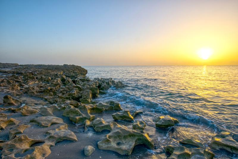 Sunrise Over Ocean And Limestone Rock Formations. At Coral Cove Park royalty free stock image