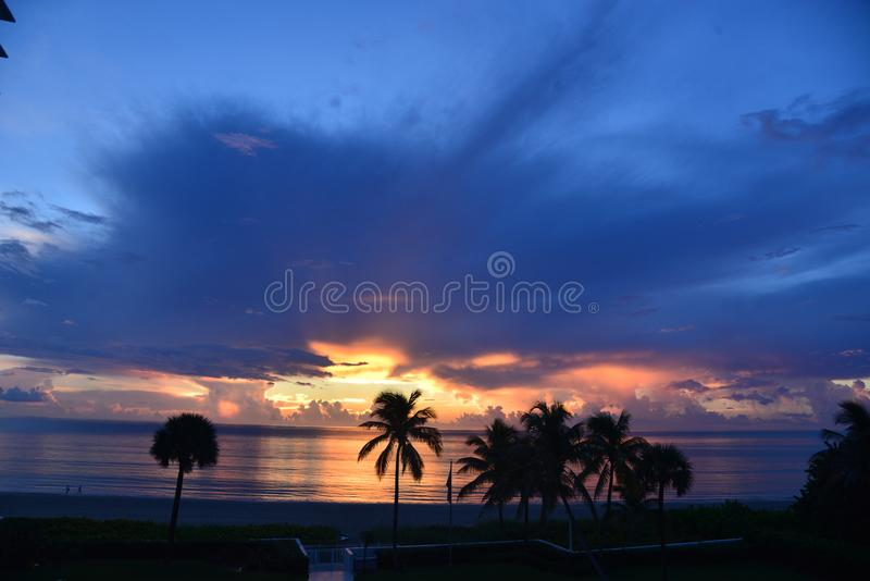 Clouds over the ocean appear blue as the sunrise begins. Sunrise over the ocean is striking for its color combinations that change as the sun begins its journey royalty free stock photography