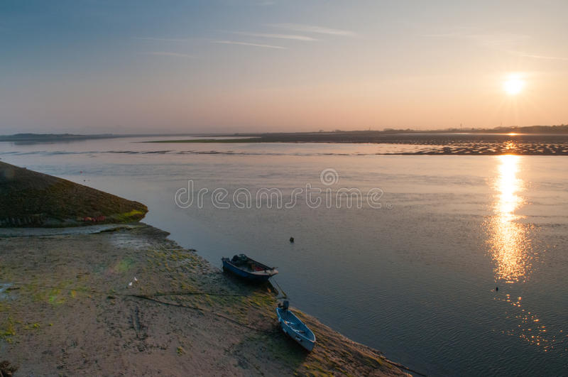 Sunrise over ocean water. Sun rising over the water over the estuary leading to the ocean royalty free stock photo